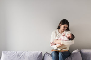Woman With Book Holding Newborn Baby