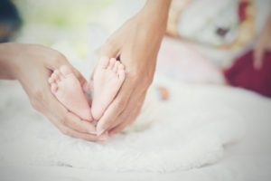 Newborn Baby's Feet In The Mother's Hands